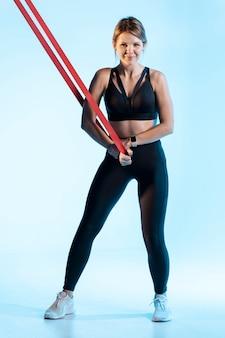 Vorderansichtfrau, die mit gummiband trainiert