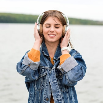 Vorderansichtfrau, die musik am meer hört