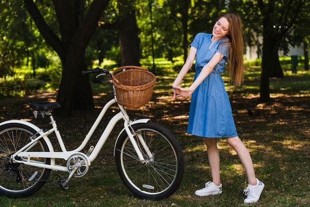 Vorderansichtfrau, die nahe bei fahrrad aufwirft