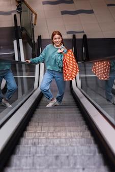 Vorderansichtfrau, die papiertüte auf rolltreppe hält