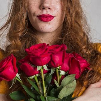 Vorderansichtfrau, die schöne rosen anhält