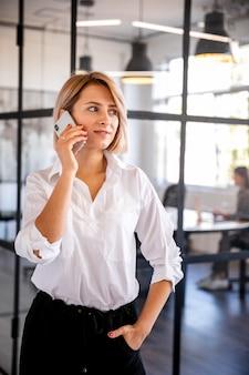 Vorderansichtfrau, die über telefon spricht