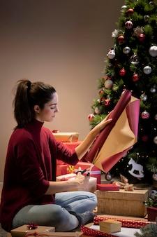 Vorderansichtfrau zu hause, die geschenke einwickelt