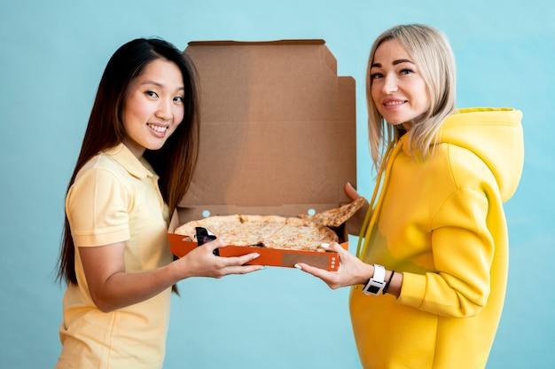 Vorderansichtfrauen, die eine schachtel mit pizza halten