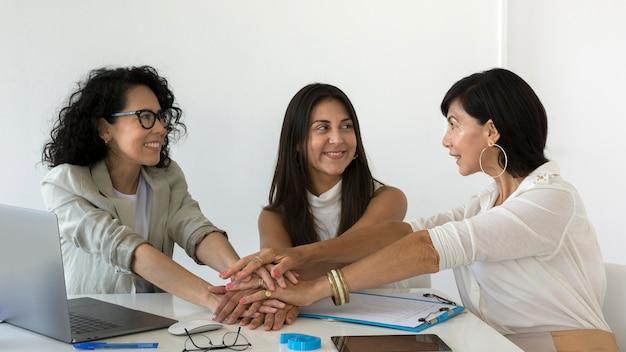 Vorderansichtfrauen, die sich für ein neues projekt zusammenschließen