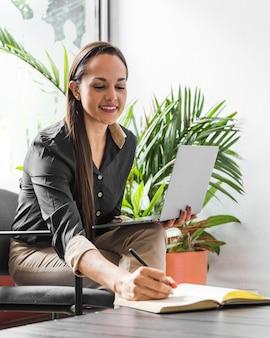 Vorderansichtfrauenschreiben auf notizbuch bei der arbeit