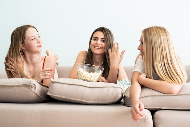 Vorderansichtfreunde, die auf sofa klatschen