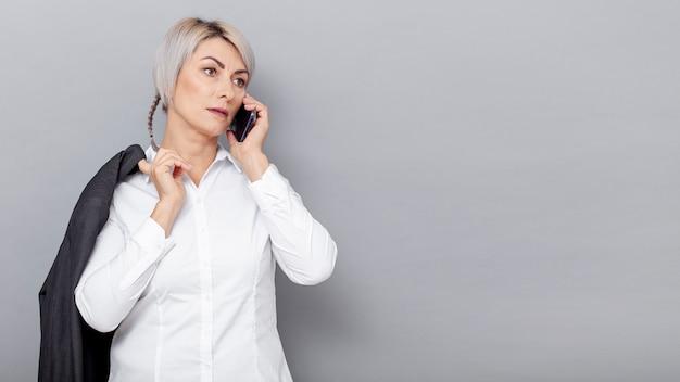 Vorderansichtgeschäftsfrau, die über telefon spricht