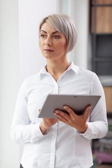 Vorderansichtgeschäftsfrau im büro mit tablette
