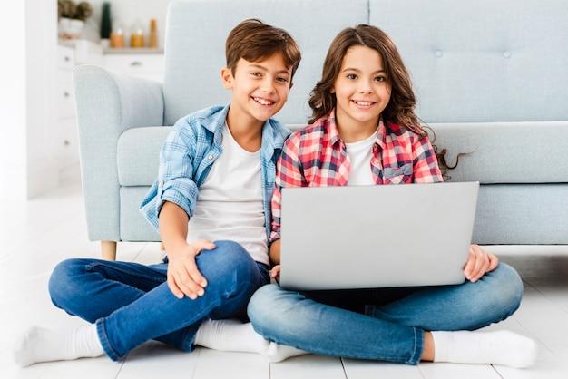 Vorderansichtgeschwister auf boden unter verwendung des laptops