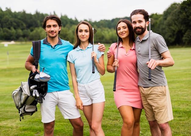 Vorderansichtgruppe golfspieler, die an der kamera lächeln