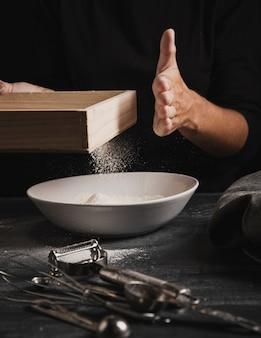 Vorderansichthand, die mehl in der platte siebt