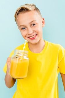 Vorderansichtjunge, der die orange frisch trinkt
