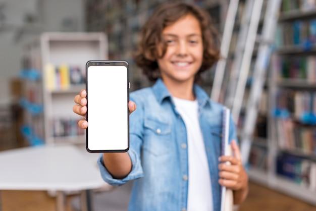 Vorderansichtjunge, der ein leeres bildschirmtelefon in der bibliothek hält