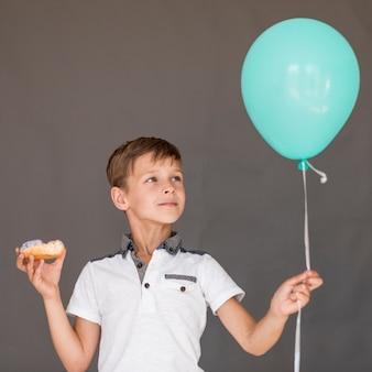 Vorderansichtjunge, der einen ballon und einen donut hält