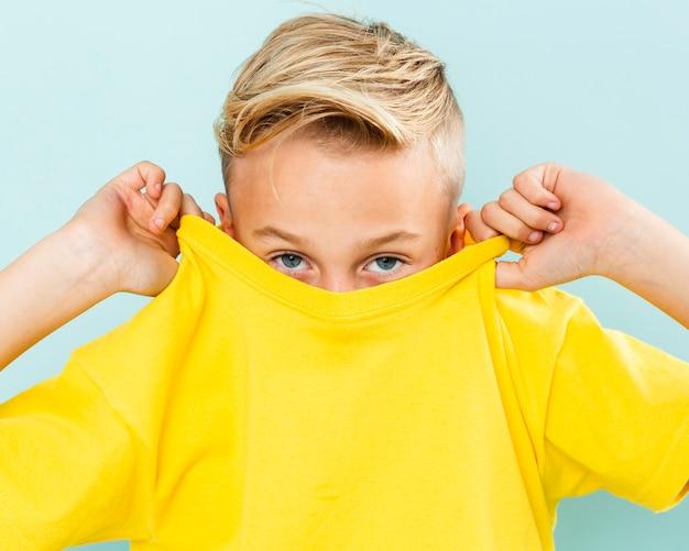 Vorderansichtjunge, der sein gesicht mit t-shirt bedeckt