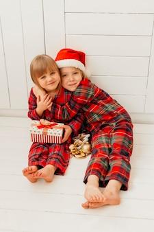 Vorderansichtjunge, der seine schwester am weihnachtstag umarmt