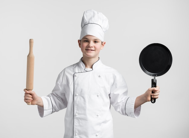 Vorderansichtjunge verkleidet als koch, der werkzeuge hält