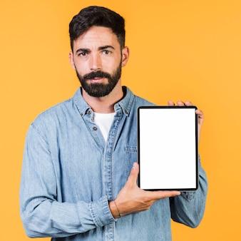 Vorderansichtkerl, der eine tablette hält