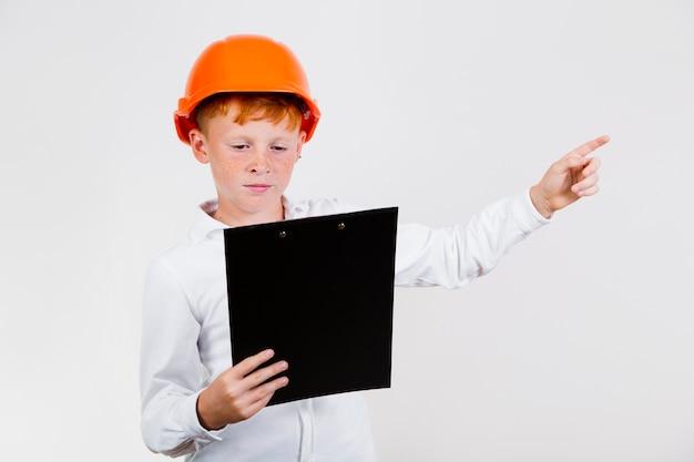 Vorderansichtkind, das als bauarbeiter aufwirft
