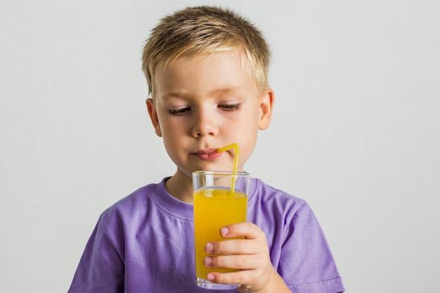 Vorderansichtkindertrinkender saft mit einem strohhalm