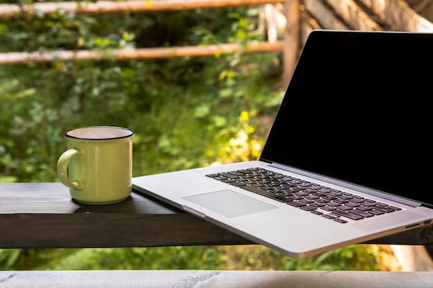 Vorderansichtlaptop und -tasse kaffee