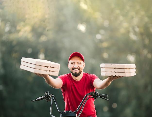 Vorderansichtlieferer, der pizzakästen hält