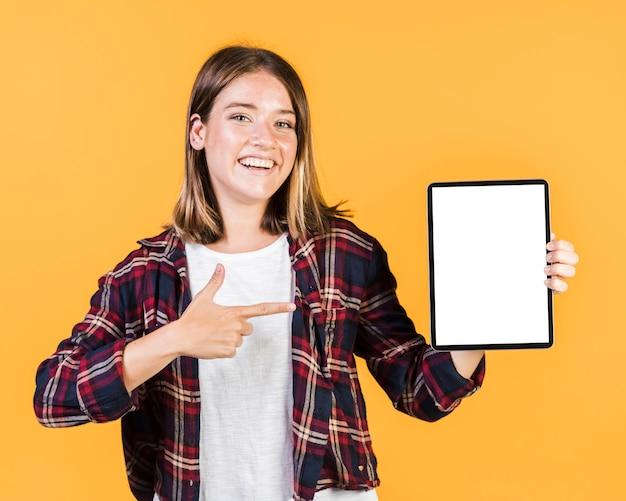 Vorderansichtmädchen, das auf eine tablette zeigt