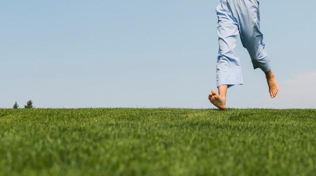 Vorderansichtmädchen, das auf gras geht