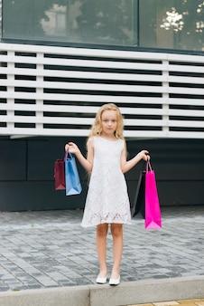 Vorderansichtmädchen, das einkaufstaschen hält