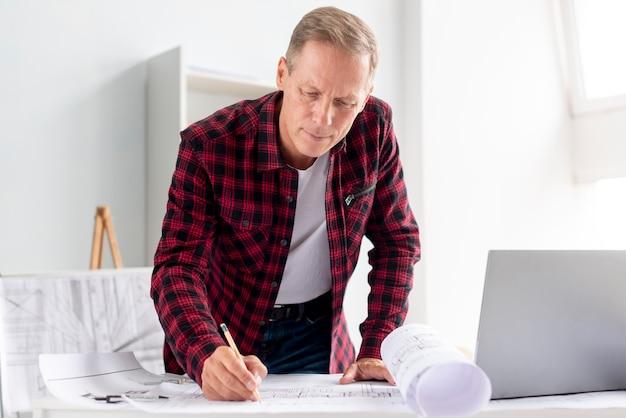 Vorderansichtmann, der an architekturprojekt arbeitet