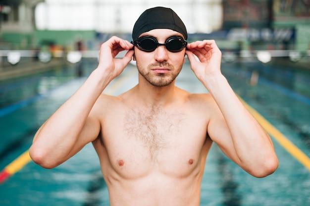 Vorderansichtmann, der auf schwimmbrille sich setzt