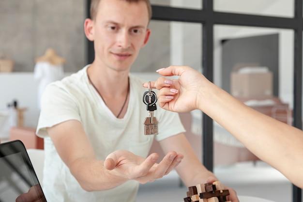 Vorderansichtmann, der die schlüssel für ein neues haus annimmt