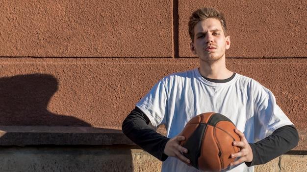 Vorderansichtmann, der einen basketball hält