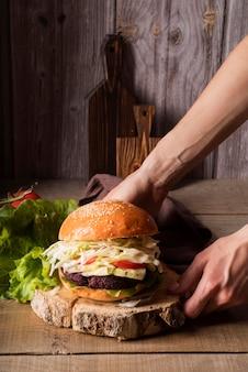 Vorderansichtmann, der einen hamburger auf ein holzbrett setzt