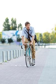 Vorderansichtmann, der fahrrad draußen reitet