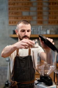 Vorderansichtmann, der in der kaffeestube arbeitet