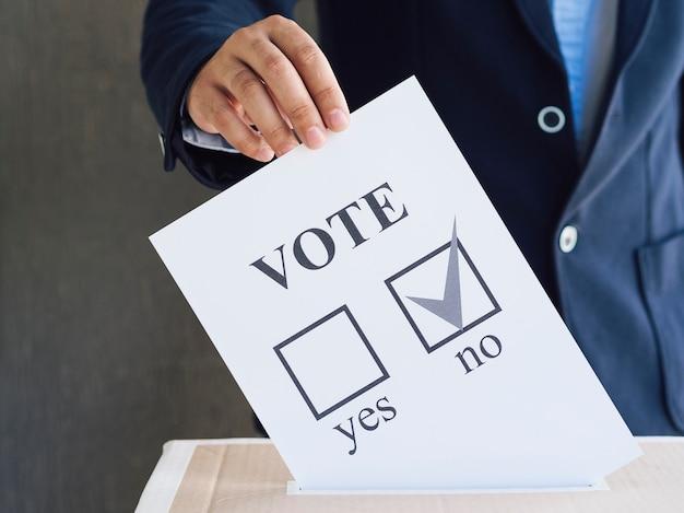 Vorderansichtmann, der seinen referendumstimmzettel in einen kasten einsetzt