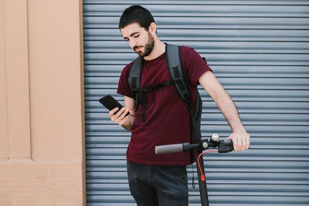 Vorderansichtmann, der telefon auf elektroroller hält