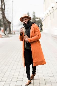Vorderansichtmann im orangefarbenen mantel, der eine tasse kaffee hält