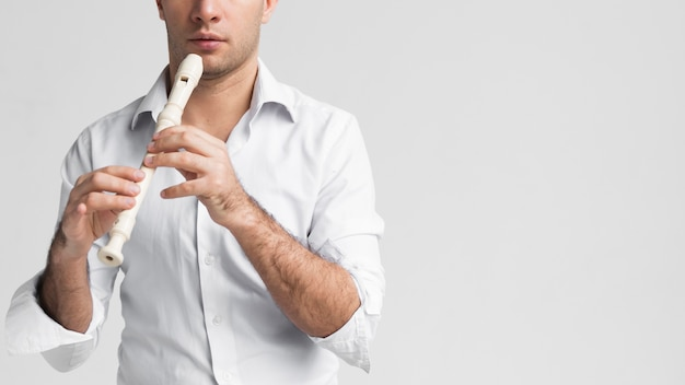 Vorderansichtmann im weißen hemd, das die flöte spielt