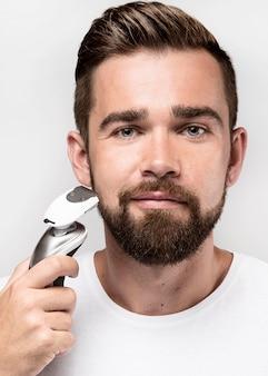 Vorderansichtmann unter verwendung einer rasiermaschine