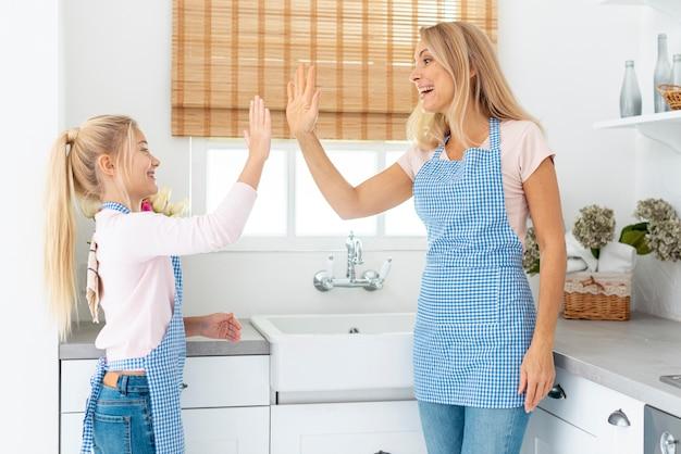 Vorderansichtmutter und tochter hallo-fünf