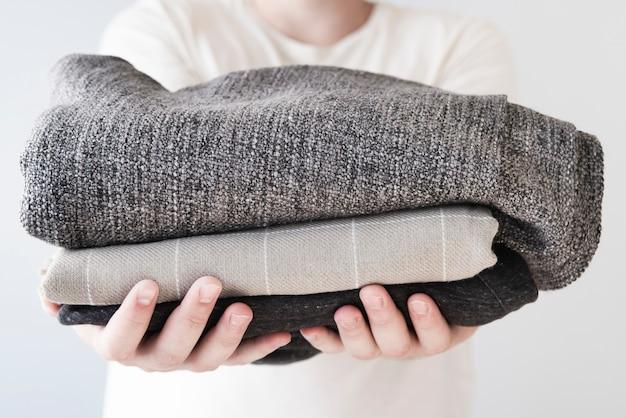 Vorderansichtperson, die gestapelte wäscherei hält