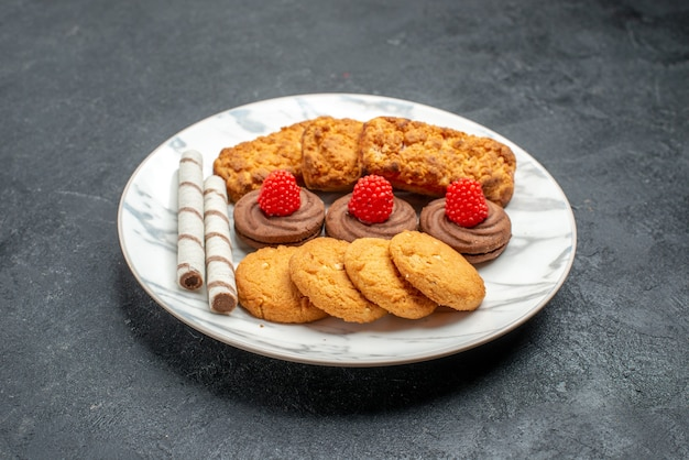 Vorderansichtplätzchen und kuchen innerhalb platte auf grauem raum