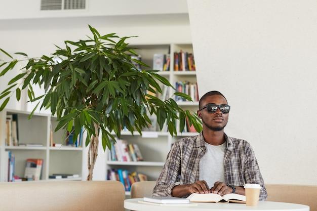 Vorderansichtporträt des blinden afroamerikanischen mannes, der braille-buch in bibliothek liest,