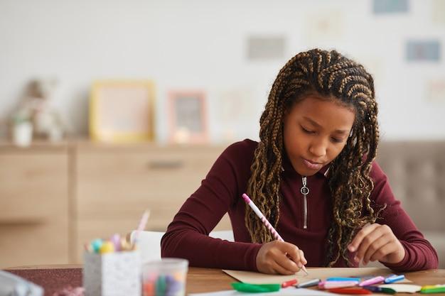 Vorderansichtporträt des jugendlichen afroamerikanischen mädchens, das hausaufgaben beim sitzen am schreibtisch im innenraum, kopierraum tut