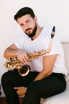 Vorderansichtporträt des mannes aufwerfend mit saxophon