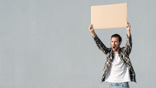 Vorderansichtprotestierender, der brett mit modell hält