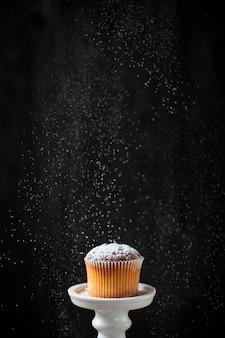 Vorderansichtpuderzucker gegossen über muffin